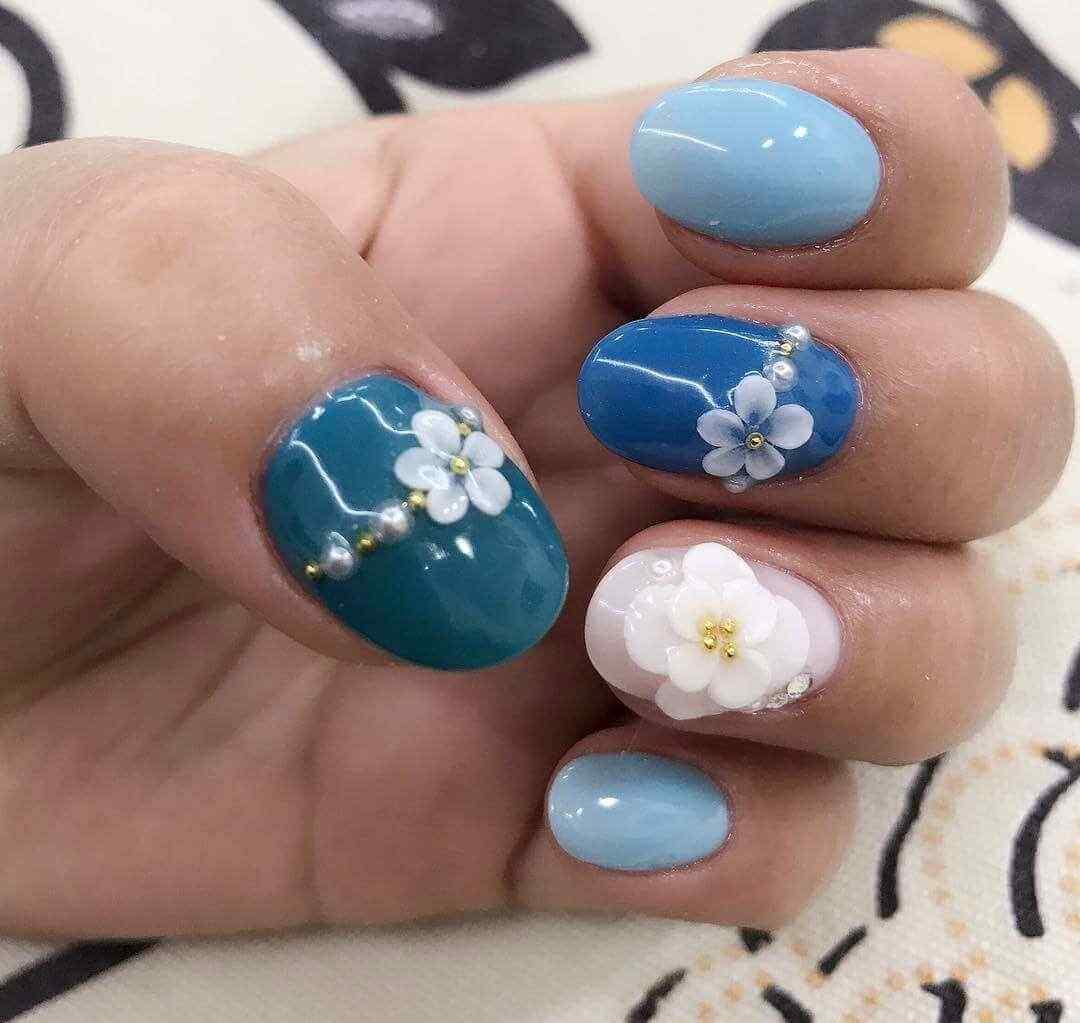 uñas azul celeste con flores blancas