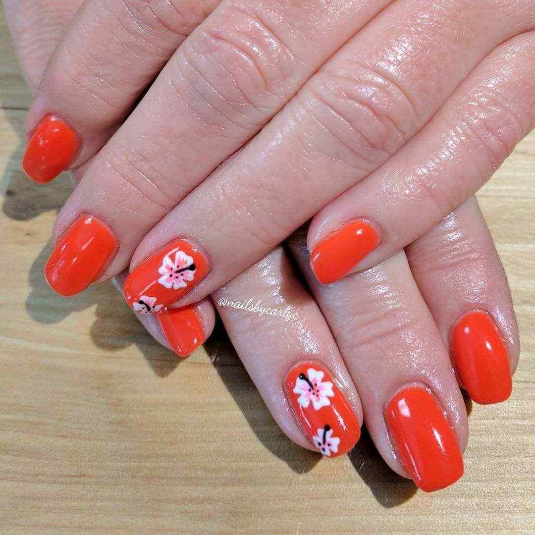 uñas decoradas naranja con flores blancas