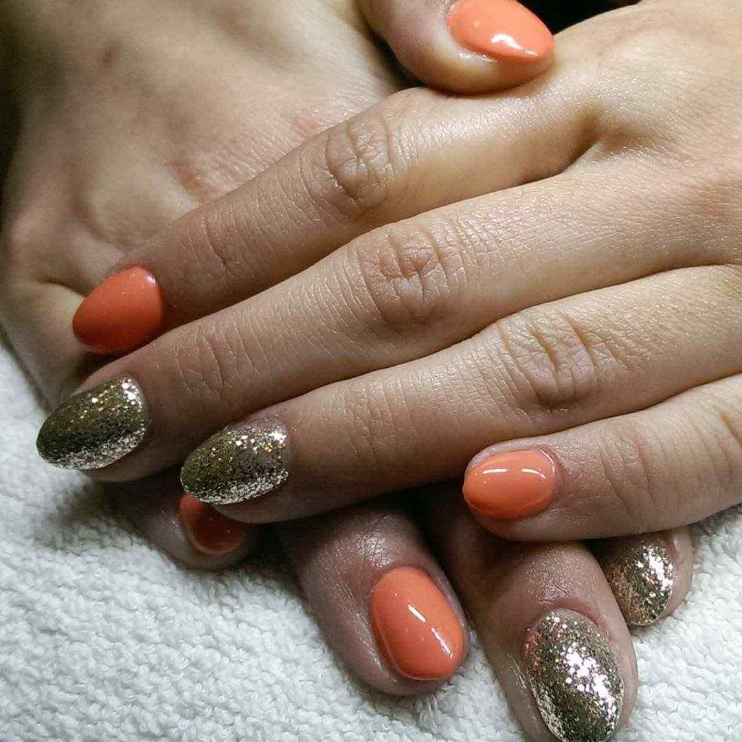 Nails decorated orange with gold