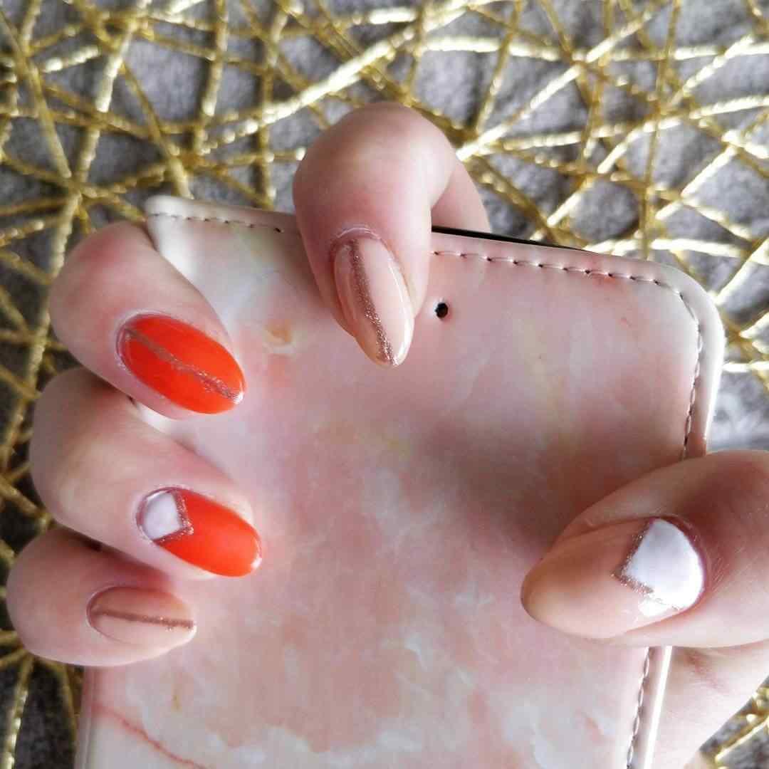 uñas elegantes naranja con lineas doradas