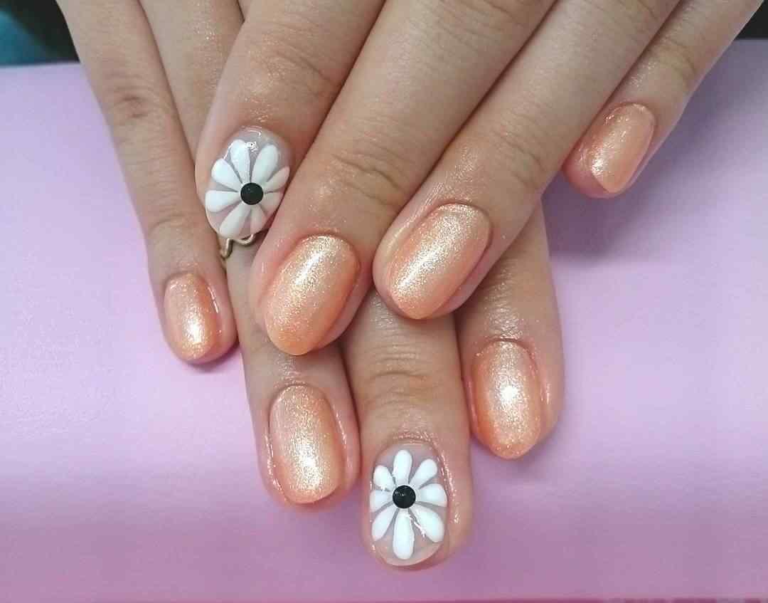 uñas naranja con flores blancas