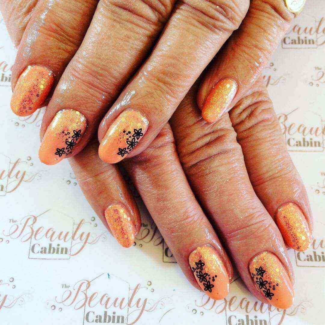 uñas naranja con flores negras