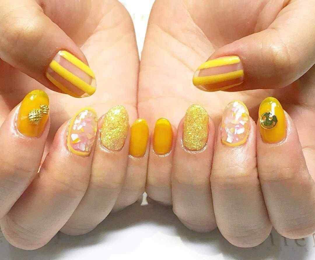 diseño de uñas amarillas con glitter