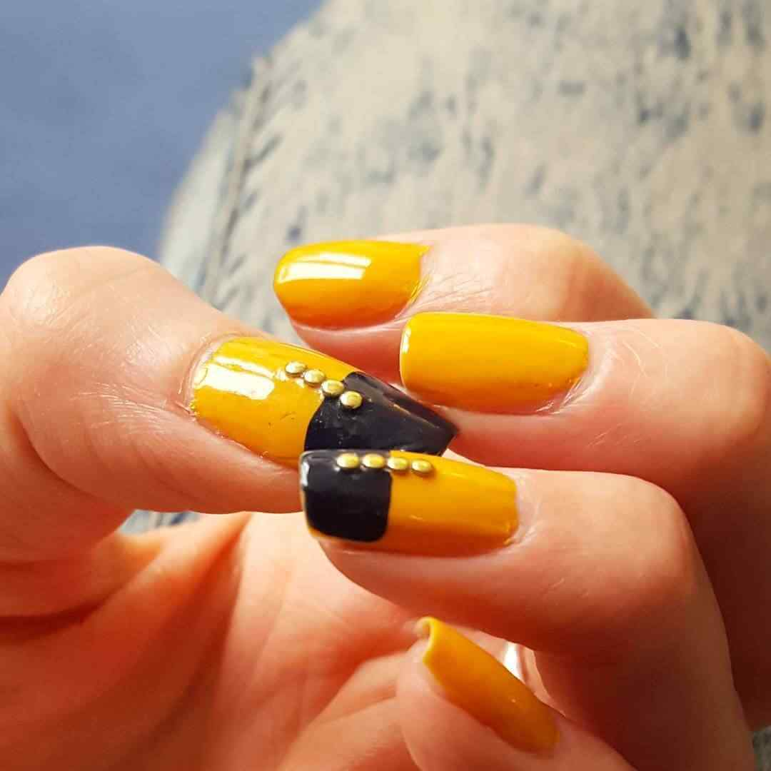 uñas amarillas con negro y piedritas doradas