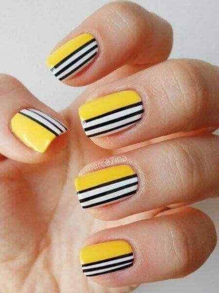 uñas amarillas decoradas con lineas blancas y negras