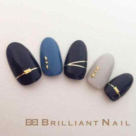 uñas azules con accesorios dorados
