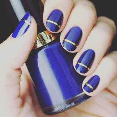 uñas azules con cinta dorada
