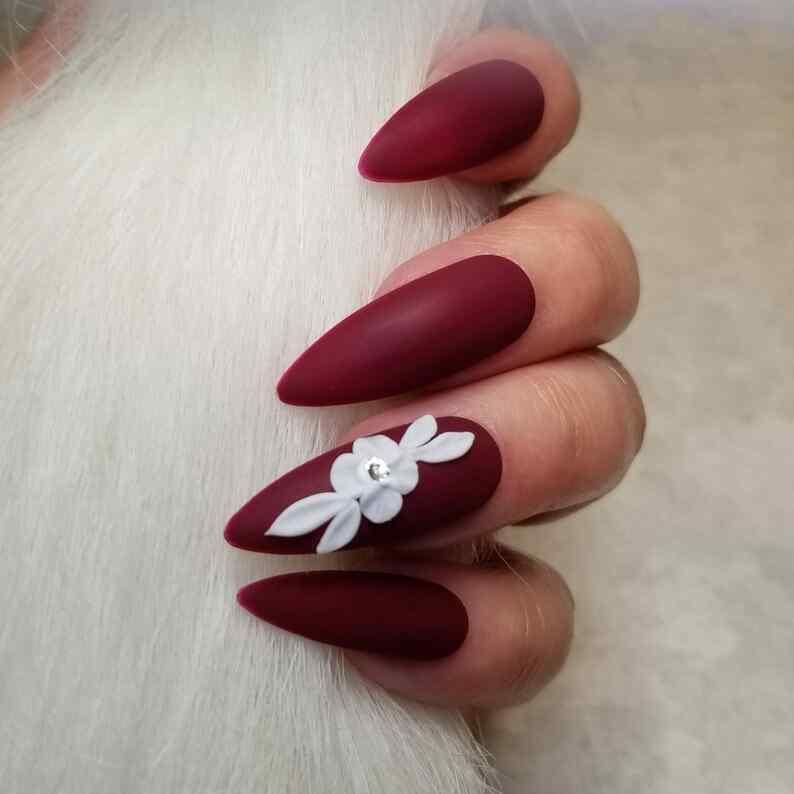 uñas vino para novia con flor blanca