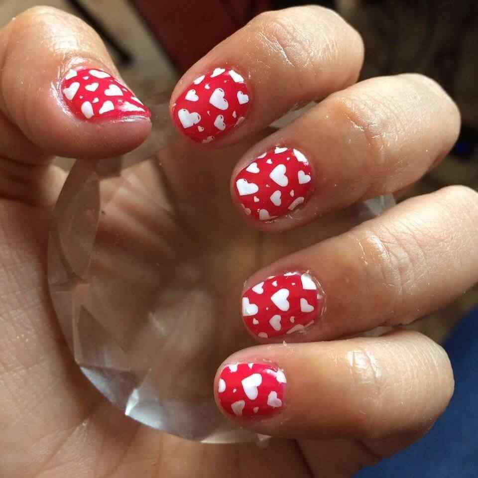 uñas rojas con corazones blancos