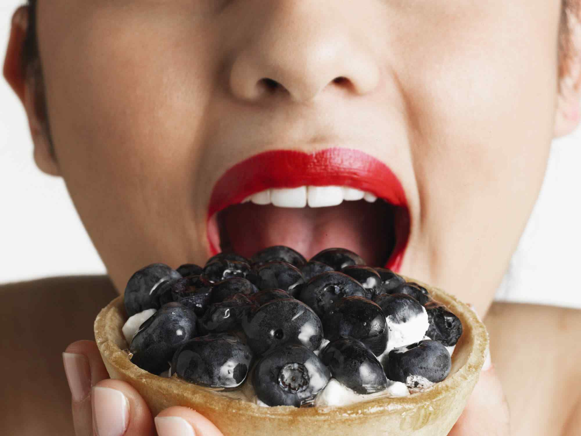 Woman wearing red lipstick, taking bite of blueberry tart, close-up of mouth