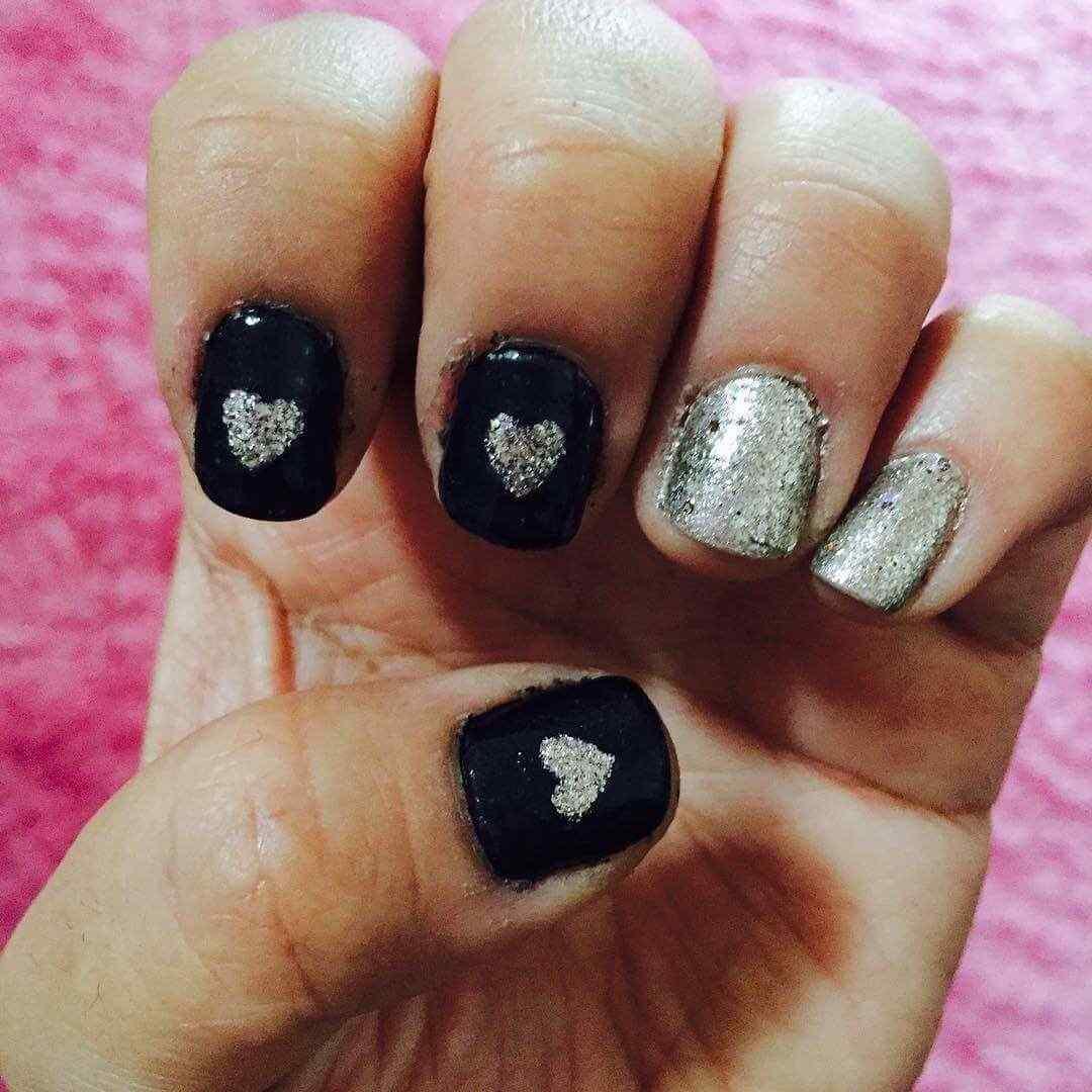 uñas plateadas con negro y corazones