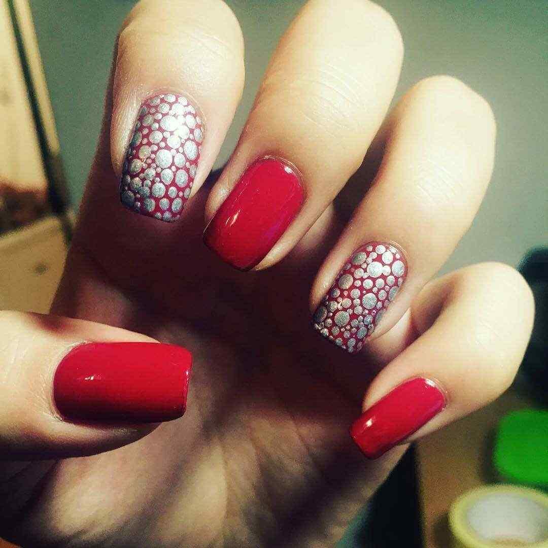 uñas plateadas y rojas con puntos