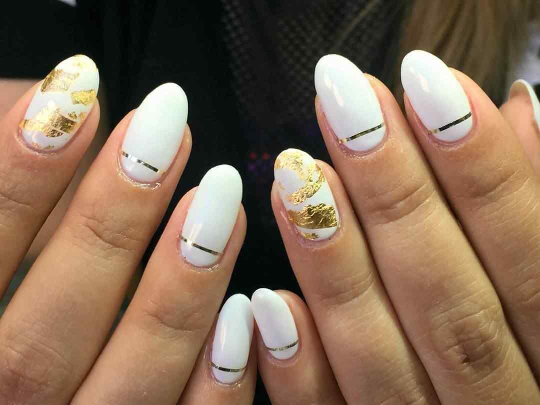 uñas blancas y doradas con cinta