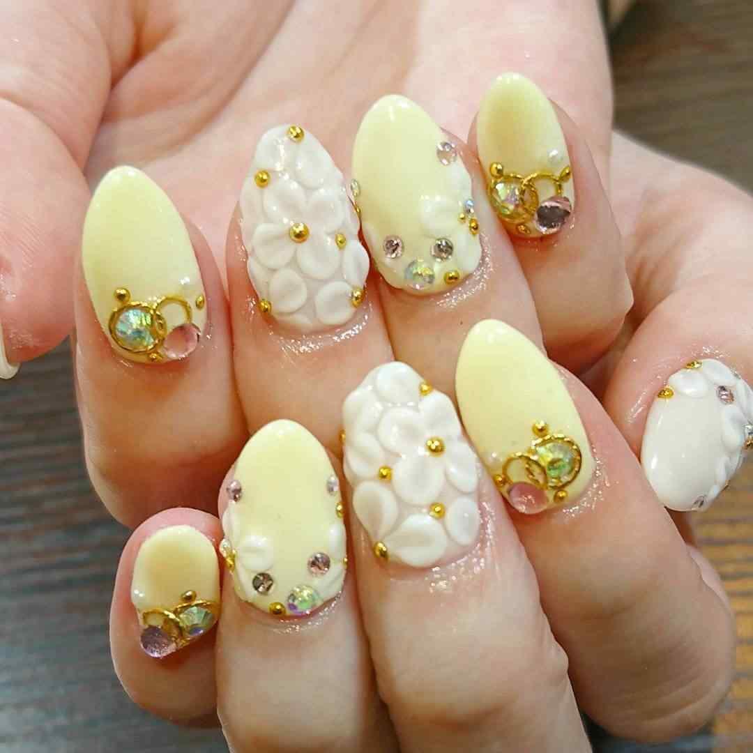 uñas amarilas con flores pegadas