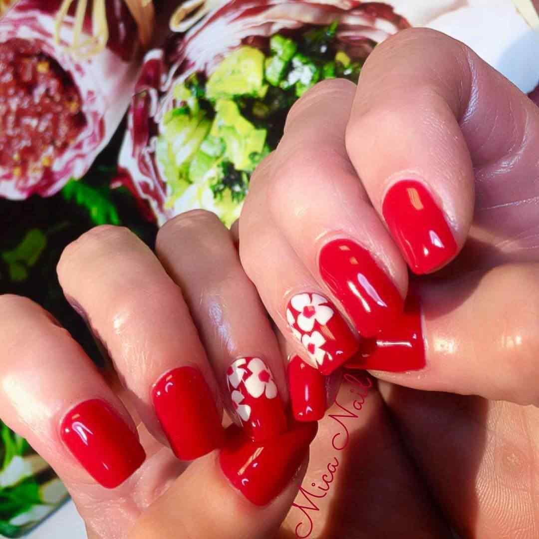 uñas rojas con flores blancas