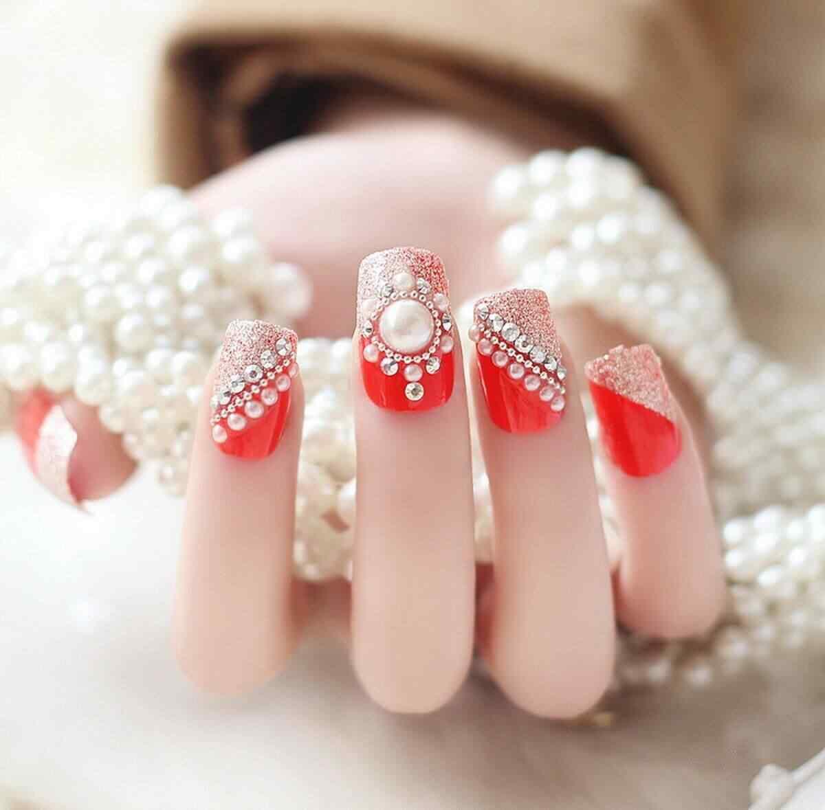 Este diseño de uñas con piedras y base roja me encanta