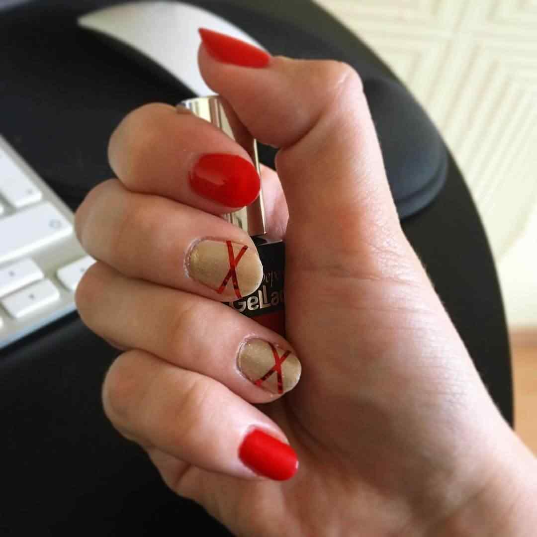 uñas  doradas con cinta roja