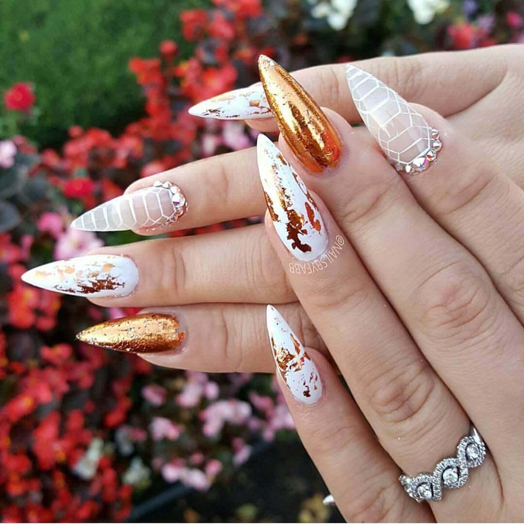 diseño de uñas doradas con blanco