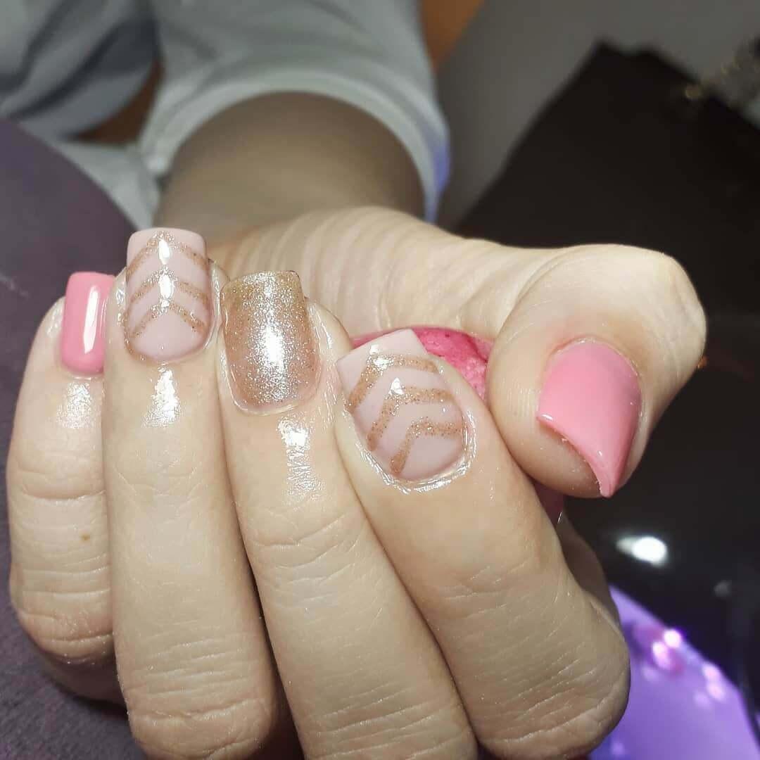 diseño de uñas doradas con rosa