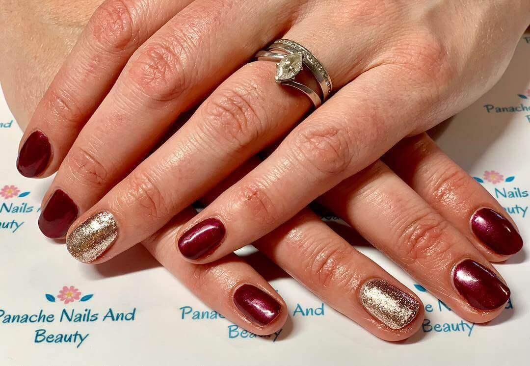 diseño de uñas doradas con vinotinto