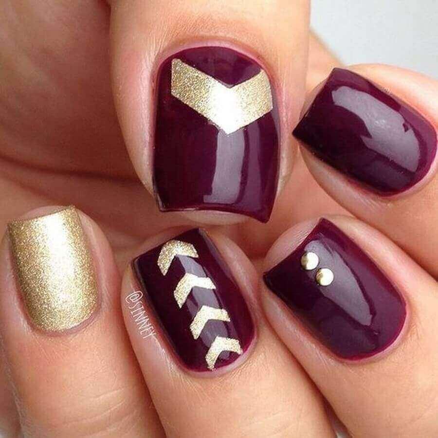 uñas doradas con color vino