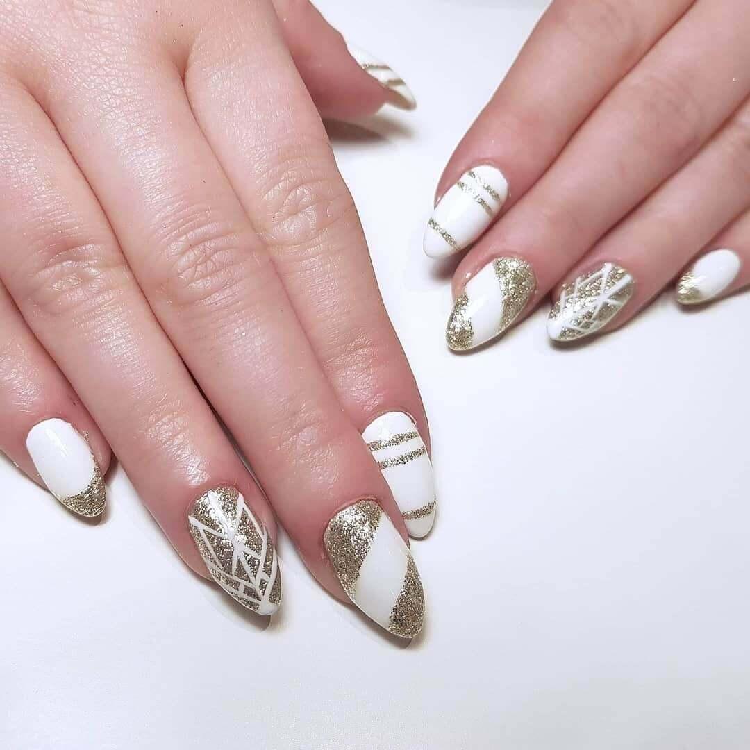 uñas doradas con estampado blanco