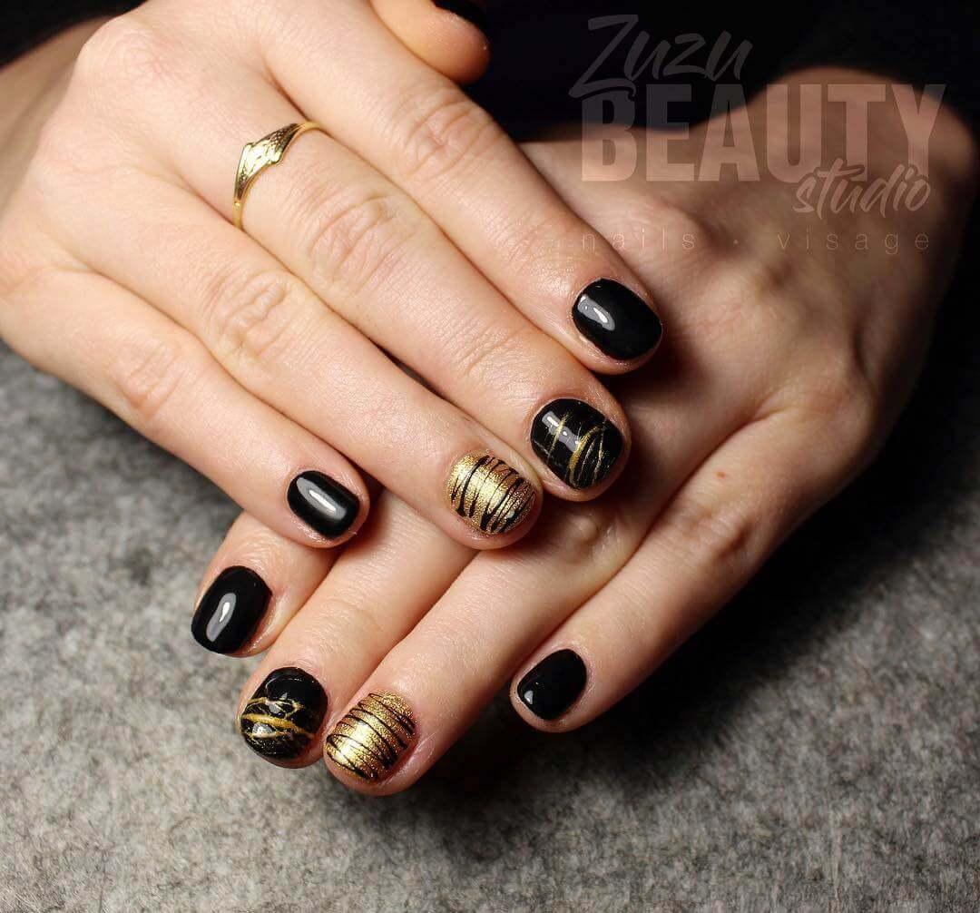 uñas doradas con lineas negras