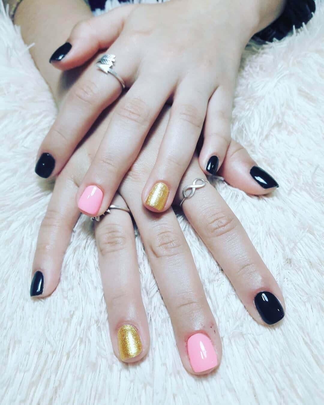 uñas doradas con negro y rosa
