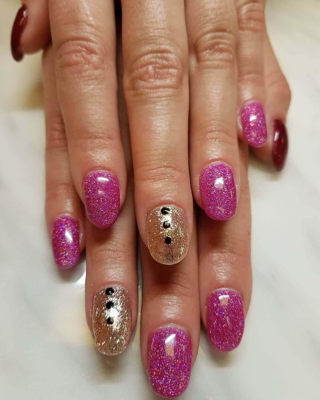 uñas doradas con rosa y puntos negros