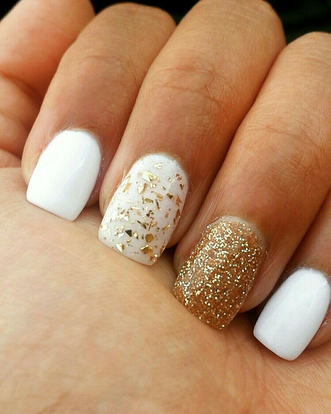 uñas doradas decoradas con blanco