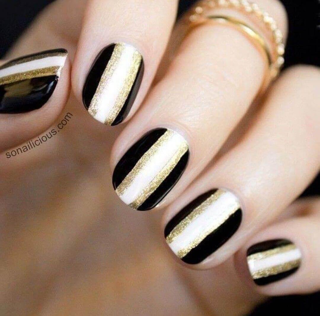 uñas doradas decoradas con negro y blanco