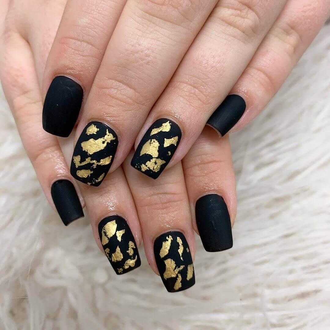 uñas doradas decoradas con negro