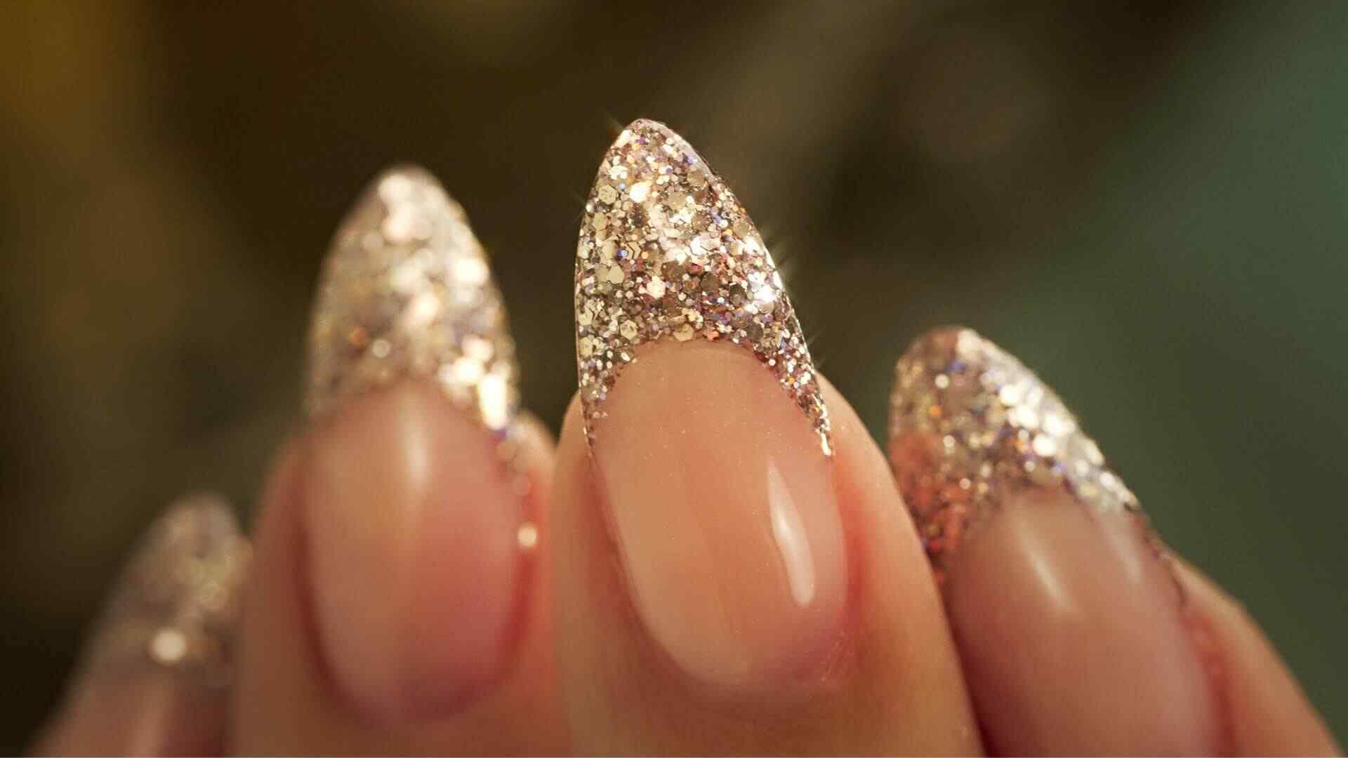 uñas acrílicas almendra doradas con brillo