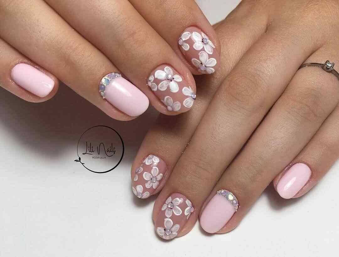 uñas delicadas rosa con flores blancas