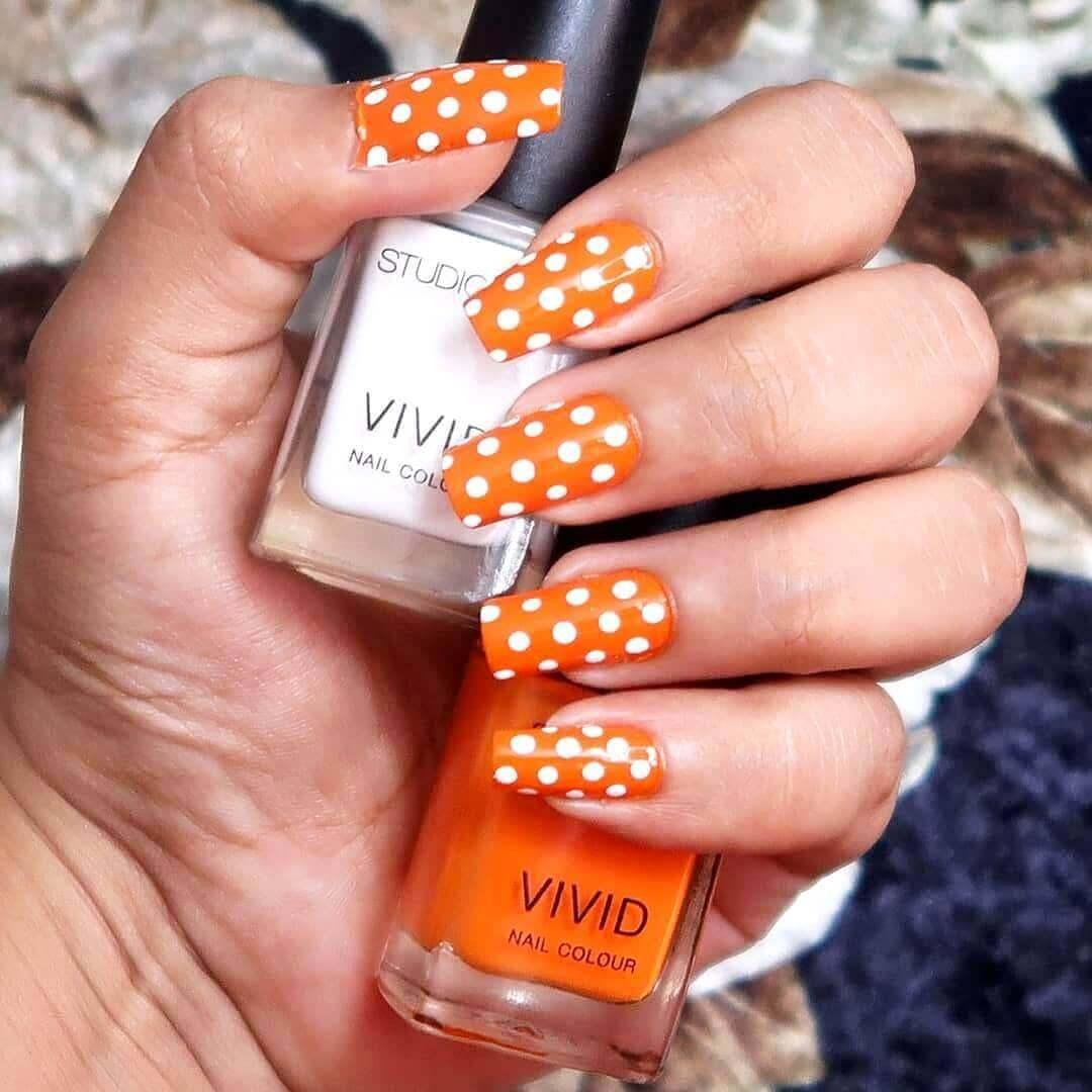 decoracion de uñas color naranja con puntos blancos