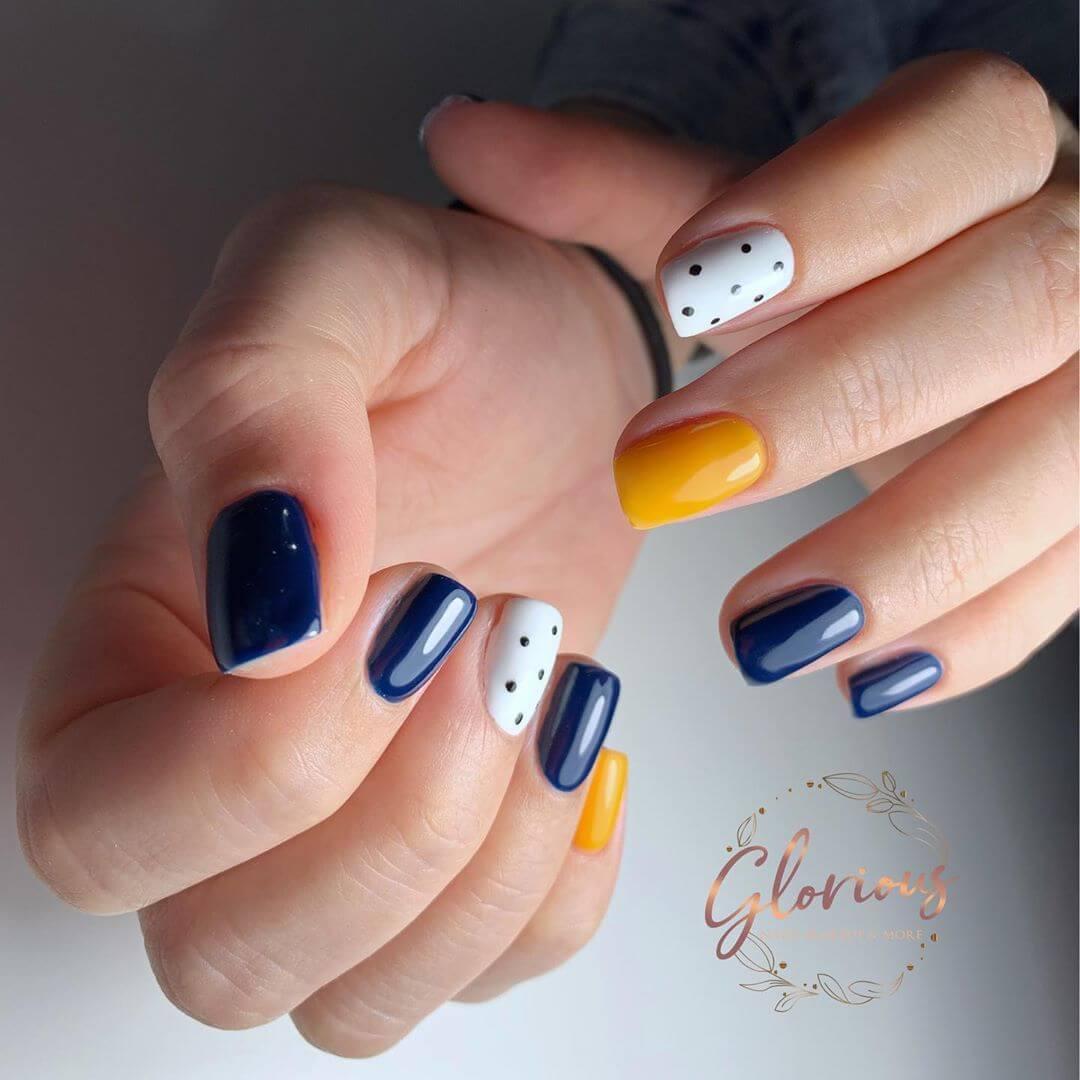 uñas amarillo mostaza con azul y blanco