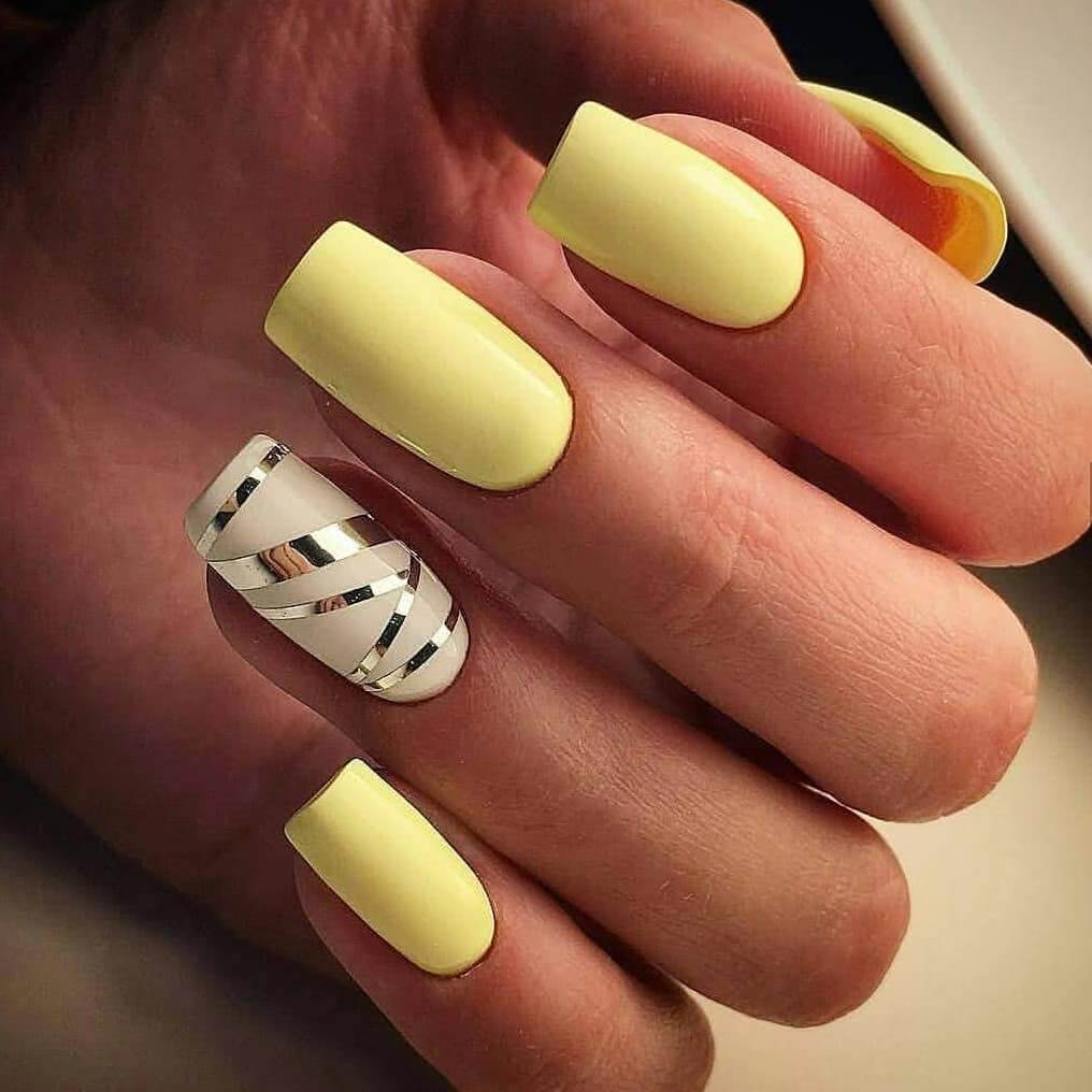 uñas amarillo pastel con cintas plateadas