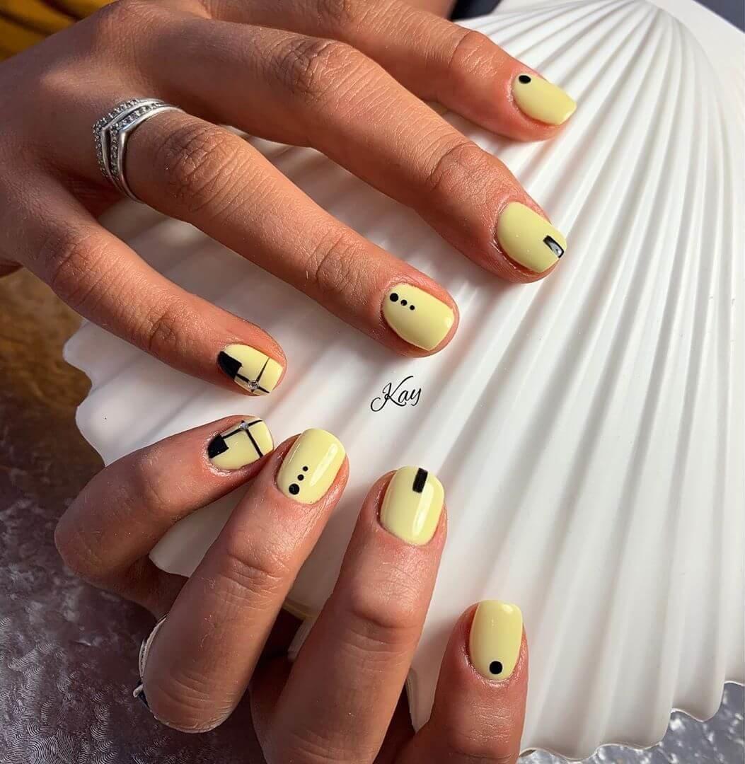 uñas amarillo pastel con negro