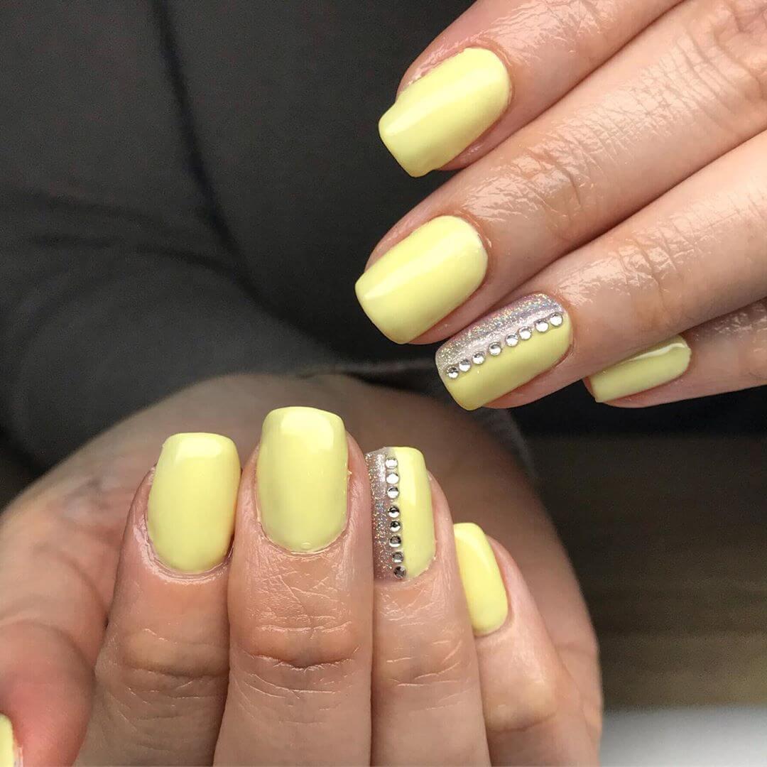 uñas amarillo pastel con piedras