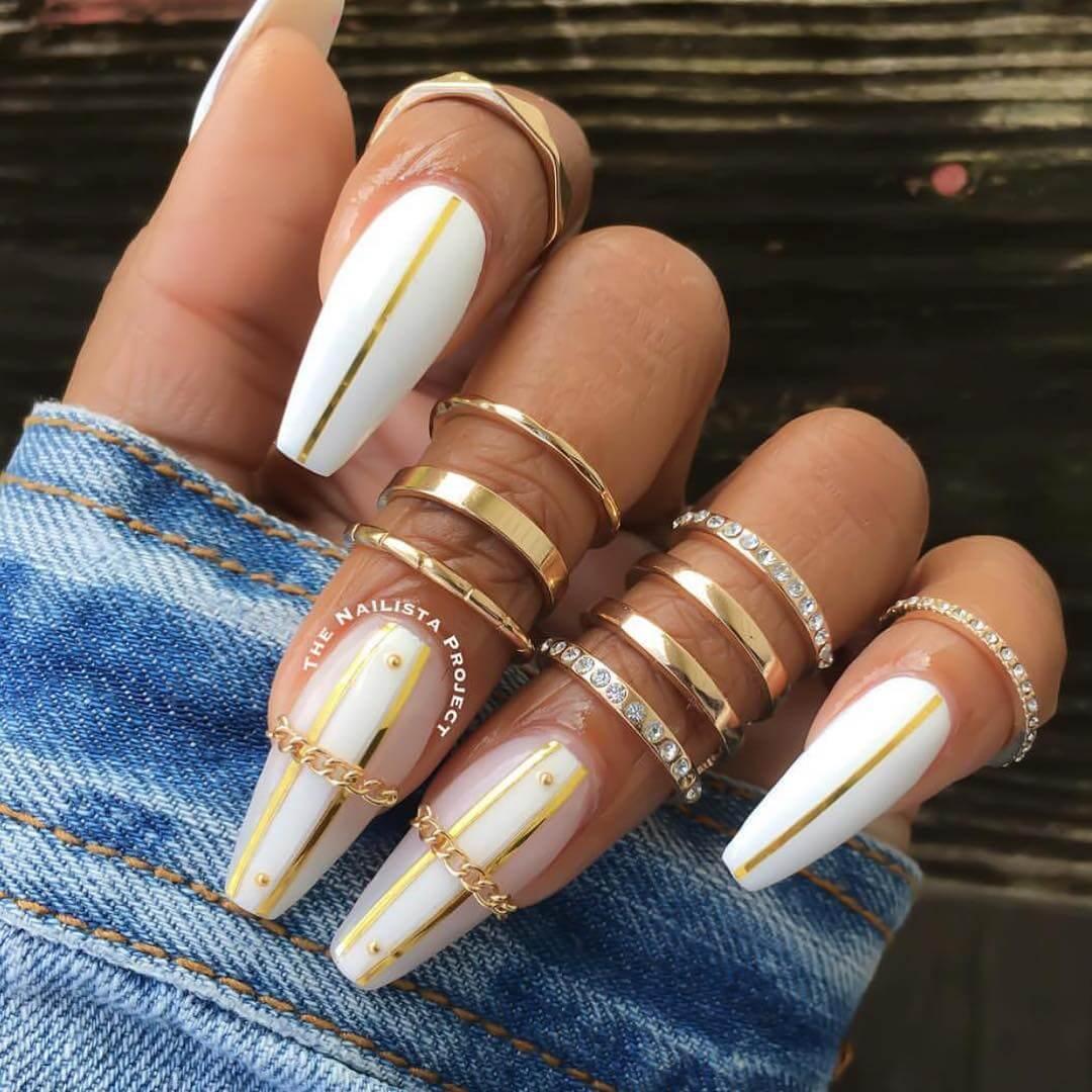 uñas blancas con cintas doradas