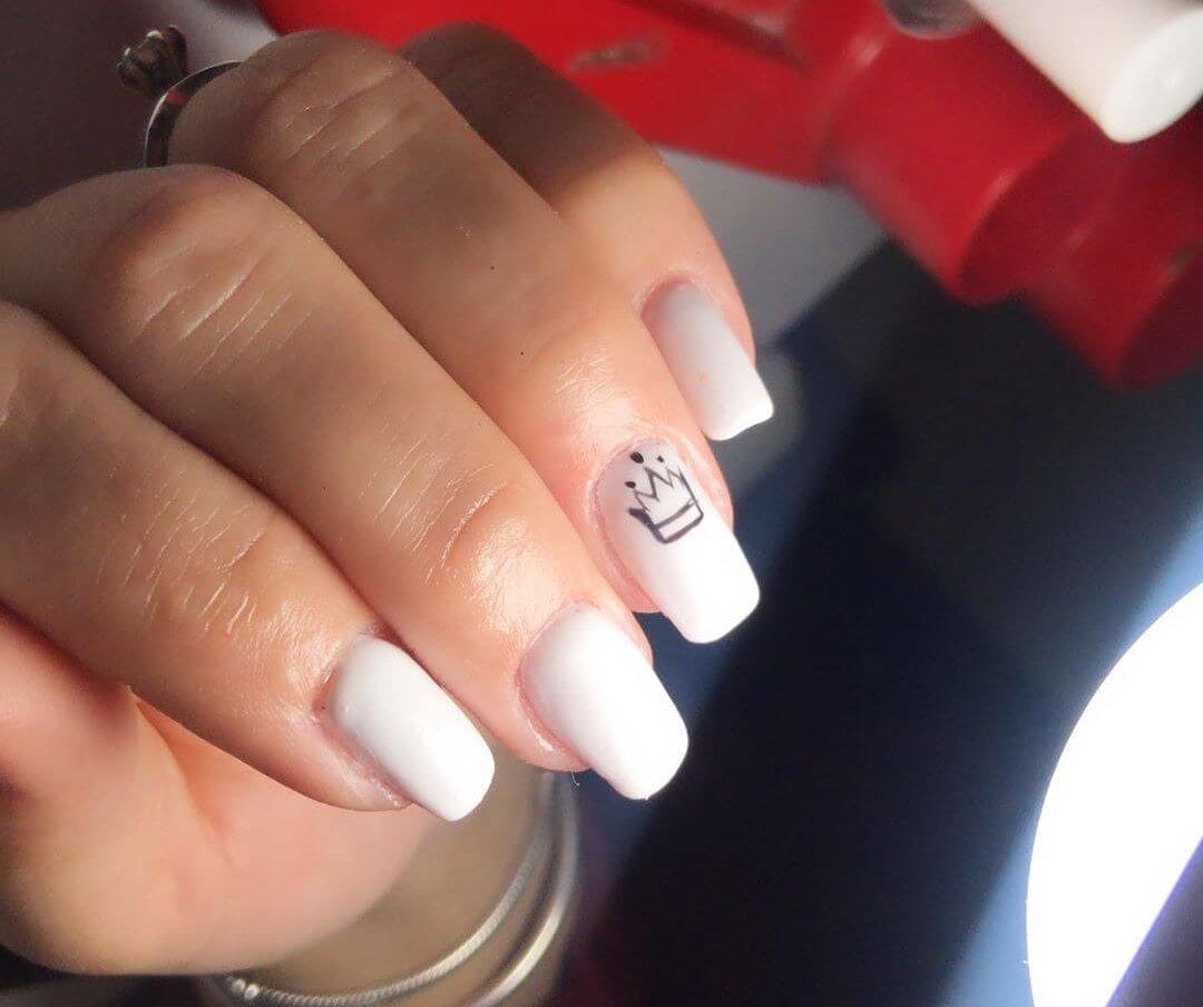 uñas blancas con diseño de corona