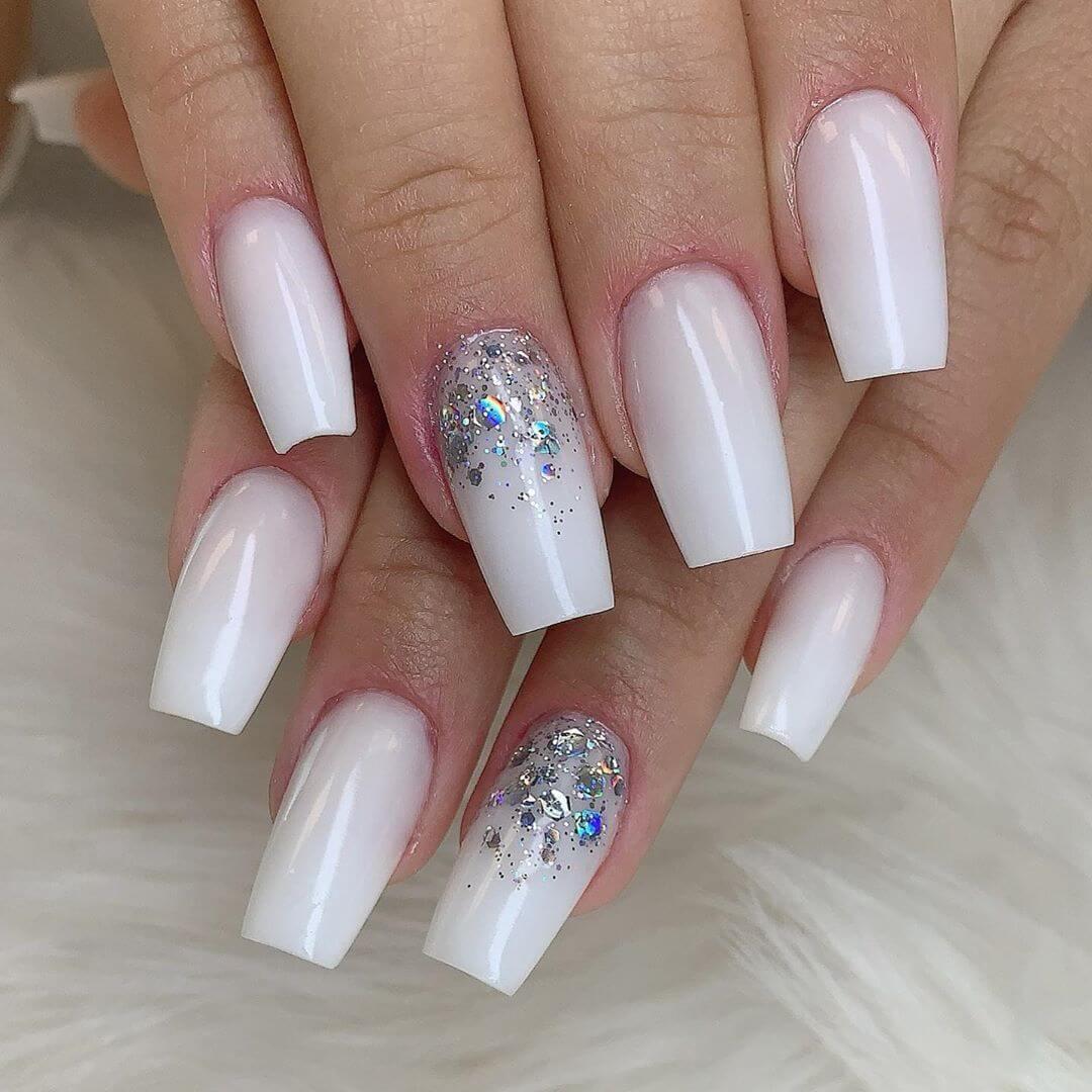 uñas blancas con esmalte glitter