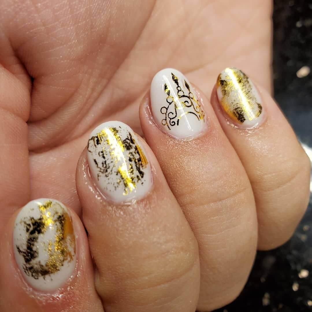 uñas blancas con estampado dorado