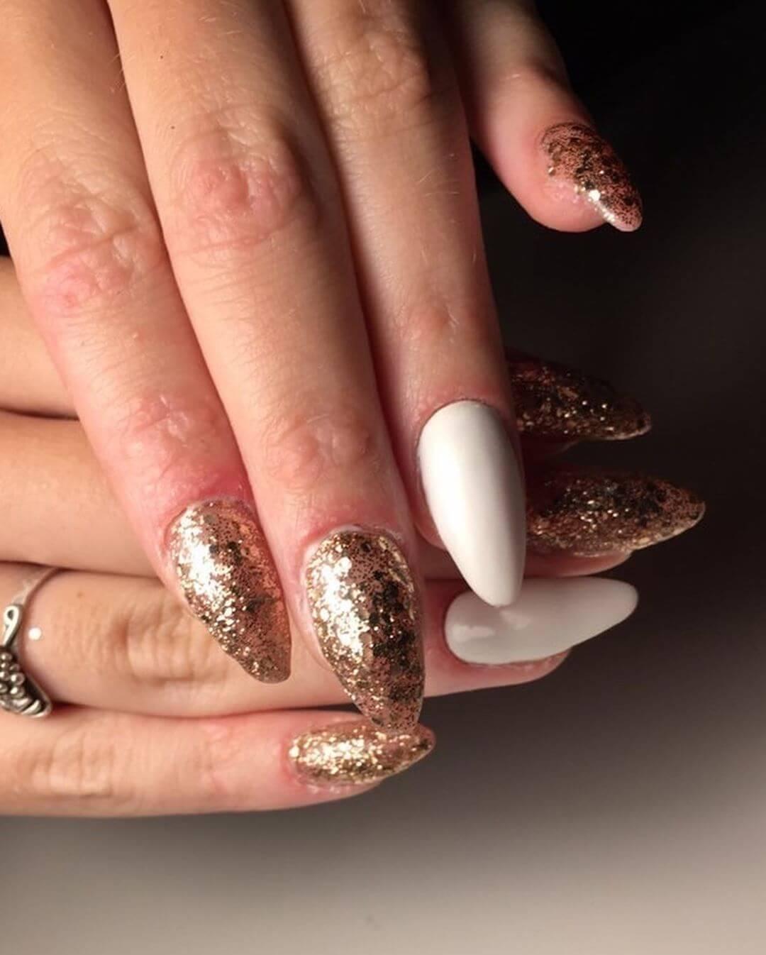 uñas blancas y doradas con brillos