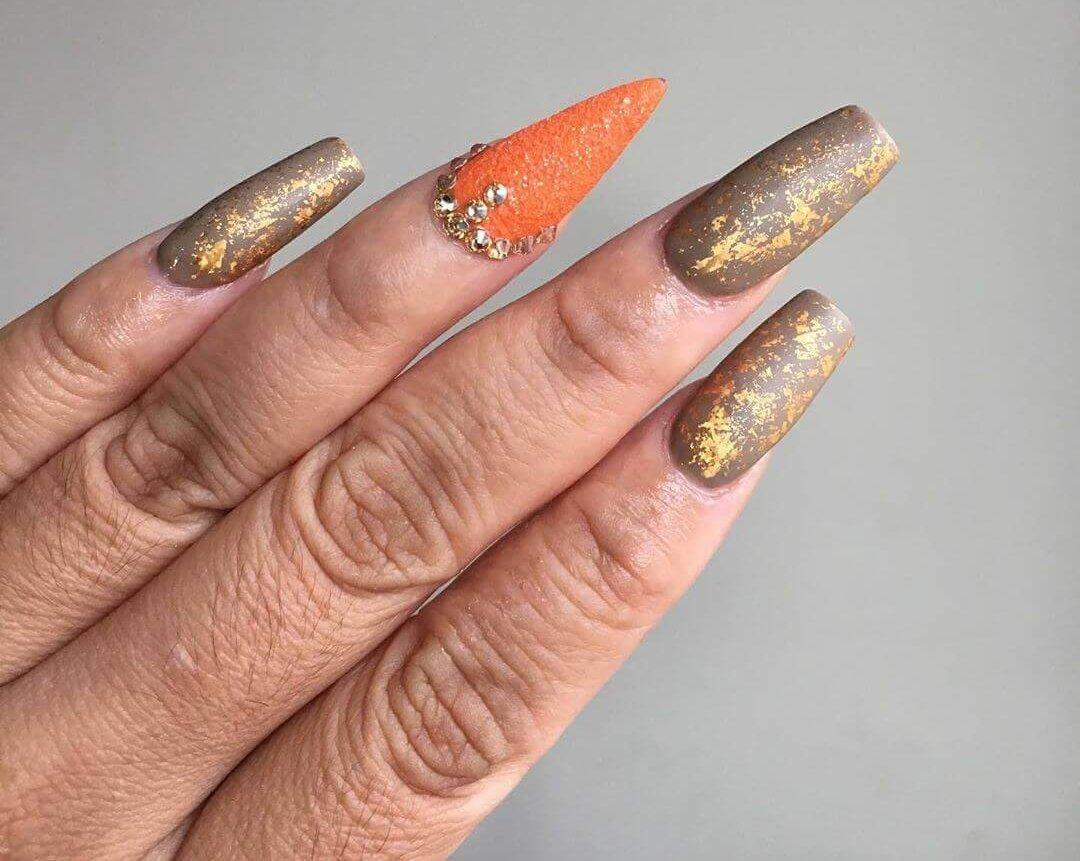 uñas color naranja con dorado y nude
