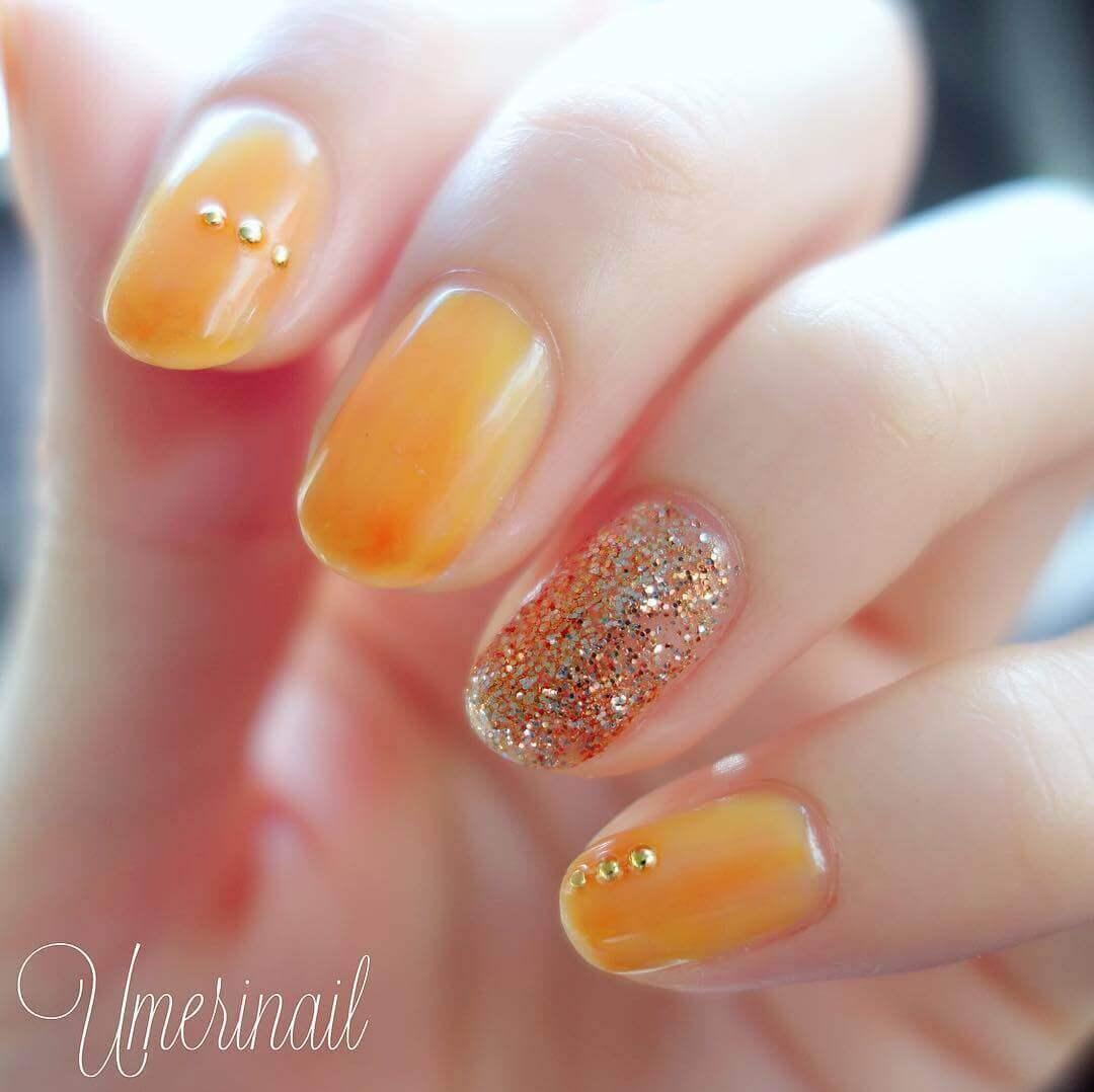 uñas color naranja con dorado
