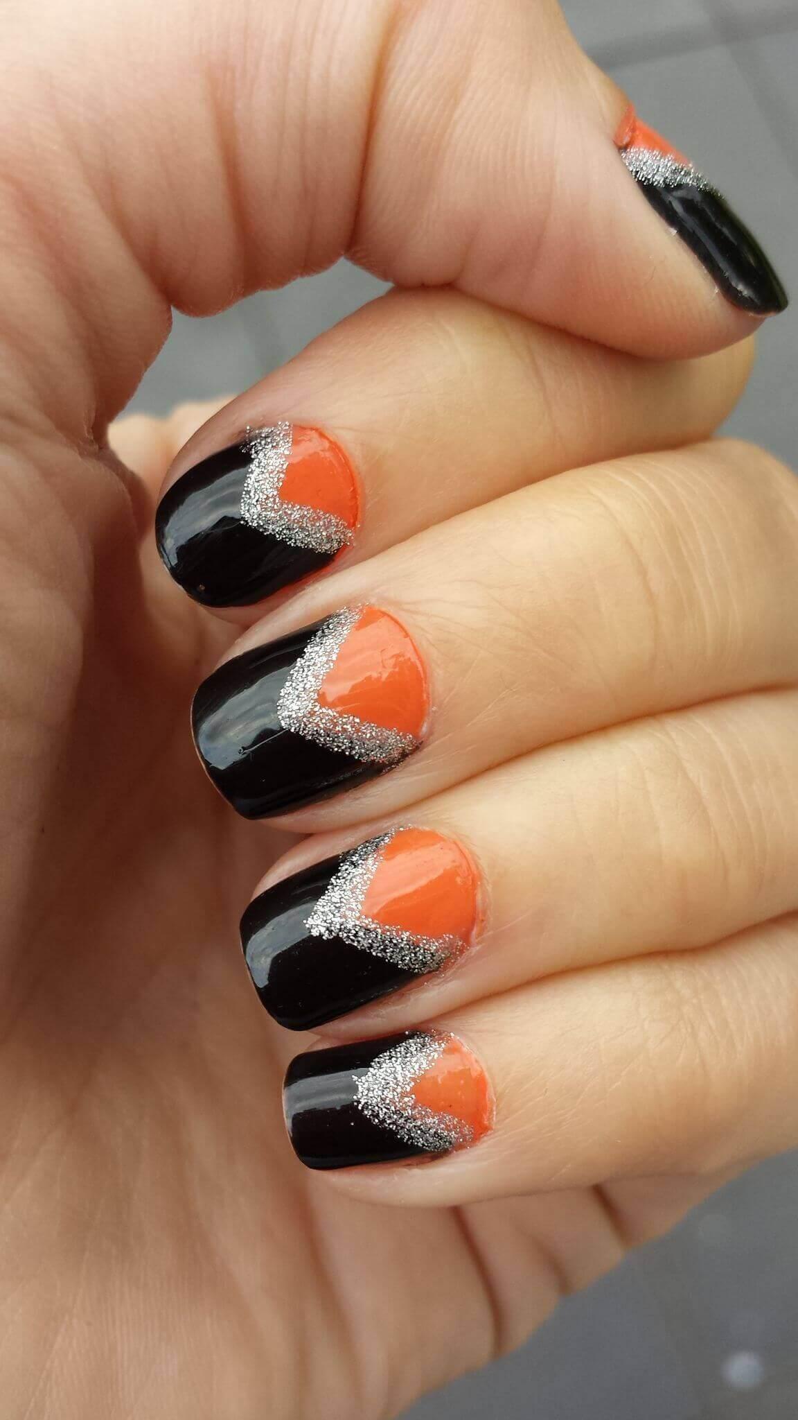 uñas color naranja con negro y plata