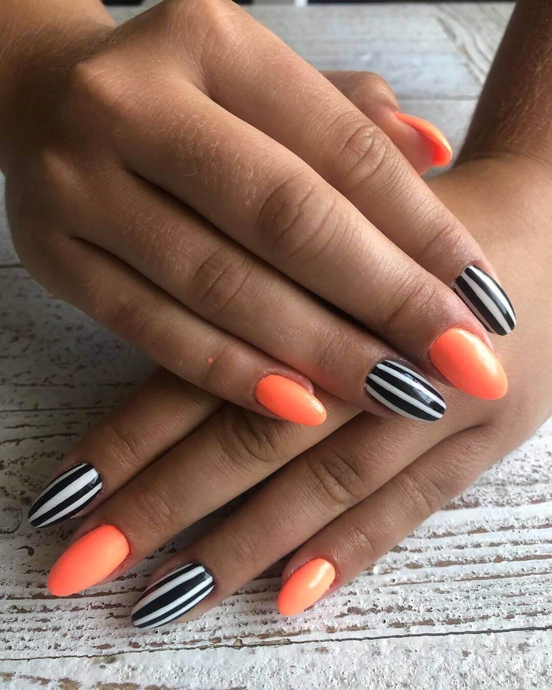uñas color naranja neon con blanco y negro