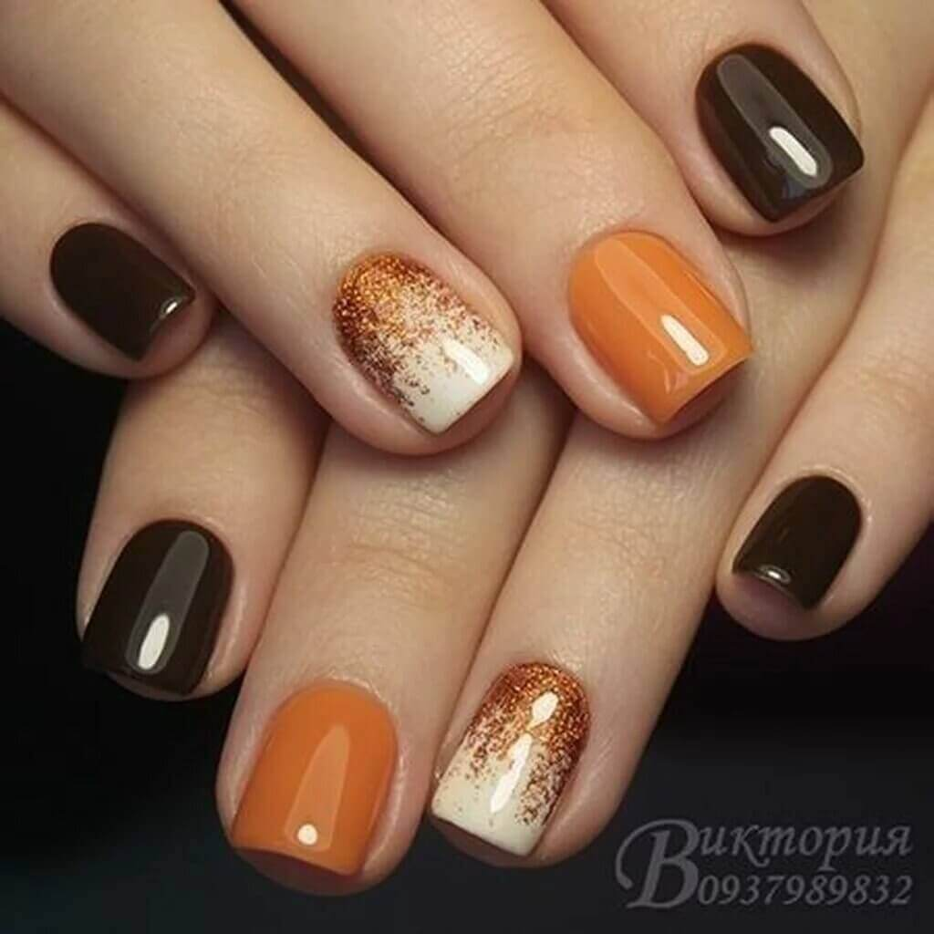 Nails decorated in orange with gold