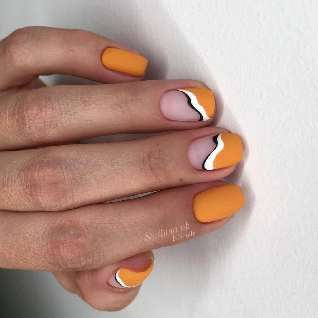 uñas naranja con blanco y negro